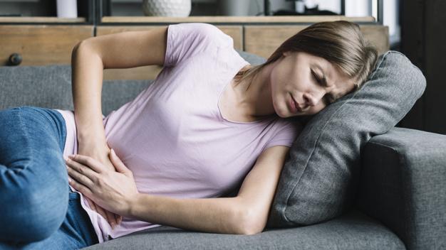 Вчені розповіли про ранні симптоми COVID-19 - коронавірус, захворюваність, дослідження, COVID-19 - young woman having stomach ache lying on sofa 23 2147953293