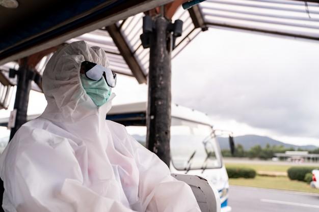 Експерти ВООЗ розслідуватимуть походження COVID-19 у Китаї - коронавірус, Китай, ВООЗ, COVID-19 - person wearing protective suit ppe with mask sit on bus to entering airplane parking outside terminal 46370 3669