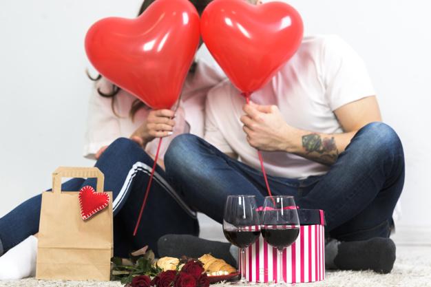 Що подарувати у День всіх закоханих - українці, подарунки, закохані, День всіх закоханих, День Валентина - couple covering faces with red heart balloons 23 2148013155