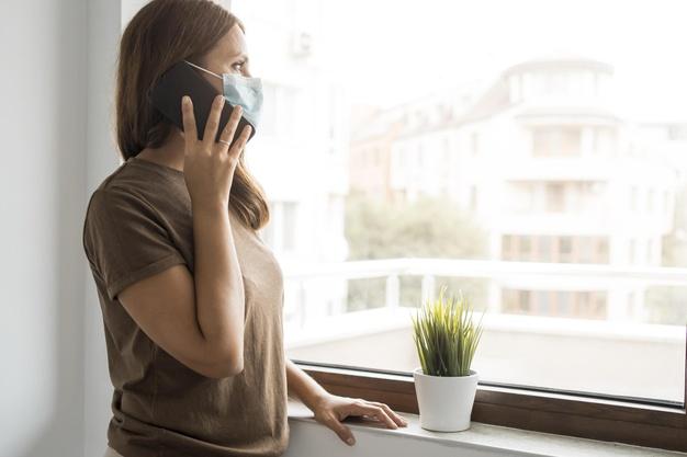 Хворих на COVID-19 в Україні стає менше - хворі, українці, статистика COVID-19, коронавірус, захворюваність - woman in quarantine at home talking on the phone while looking through the window 23 2148740981